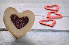 Biscuit avec la confiture et trois coeurs de papier rouges Photos libres de droits