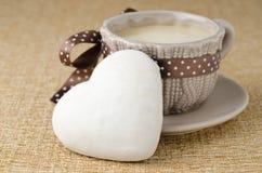 Biscuit avec le givrage sous forme de coeur et une cuvette de fin de café Images stock