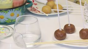 Biscuit balls with sticked chopsticks for making pop cakes lie on a plate. Near the table are glasses with icing. stock footage