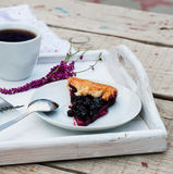 Biscuit with black currants and a cup of coffee. Black currants biscuit on a plate, a cup of black coffee and fruit for breakfast Stock Images