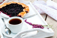 Biscuit with black currants and a cup of coffee. Black currants biscuit on a plate, a cup of black coffee and fruit for breakfast Royalty Free Stock Image