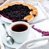 Biscuit with black currants and a cup of coffee. Black currants biscuit on a plate, a cup of black coffee and fruit for breakfast Royalty Free Stock Photos
