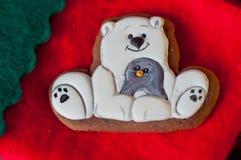 Biscuit bon de pain d'épice de vacances dans la forme de l'ours blanc avec le joint de fourrure gris s'étendant sur le fond rouge Image stock