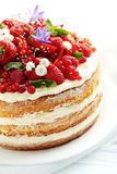 Biscuit cake. Delicious biscuit cake with berries on blue wooden table Stock Photos