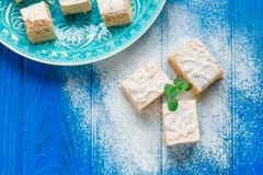Biscuit cake pie apple candy pastila decorated with mint leaves on blue wood cutting board background. Small square Royalty Free Stock Images