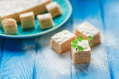 Biscuit cake pie apple candy pastila, mint leaves on blue wood cutting board background. Small square pieces paste Stock Photos