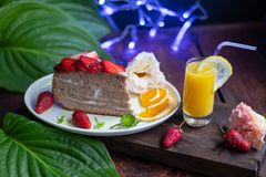 Biscuit cake with sour cream decorated with strawberries, fresh berry on a tray. stock photo