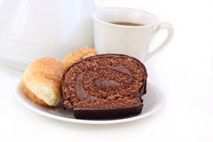 Chocolate roll. Biscuit chocolate and a croissant against the unsharp image of a coffee pot and a cup of coffee Stock Image