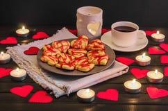 Biscuit-coeurs, coeurs de papier, bougies, boîtes avec des présents et une tasse de café noir Photographie stock