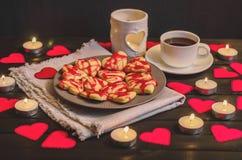 Biscuit-coeurs, coeurs de papier, bougies, boîtes avec des présents et une tasse de café noir Images stock