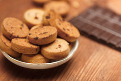 Biscuit cookies with chocolate chips standing in plate on wooden Stock Photo