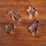 Biscuit cutter for christmas cookies on wood Royalty Free Stock Photography