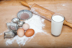 Biscuit cutters and dough ingredients on wooden table Stock Image