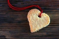 Biscuit de coeur avec le ruban rouge sur le vieux bois foncé, l'espace de copie Images stock