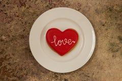 Biscuit de coeur d'un plat blanc avec amour des textes là-dessus Image libre de droits
