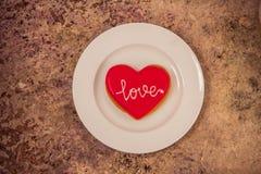 Biscuit de coeur d'un plat blanc avec amour des textes là-dessus Images libres de droits