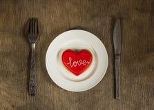 Biscuit de coeur d'un plat blanc avec amour des textes sur lui et des couverts Images stock