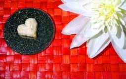 Biscuit de coeur et fleur blanche sur le fond en bois rouge Image libre de droits