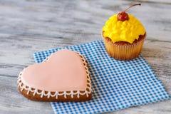 Biscuit de coeur et petit gâteau jaune Photo libre de droits