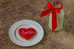 Biscuit de coeur et verre rouges de lait Images libres de droits