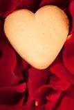 Biscuit de forme de coeur dans des pétales de rose Photographie stock libre de droits