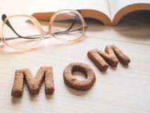 Biscuit de maman de Word au-dessus du fond en bois Le concept d'un parent célibataire Photographie stock libre de droits