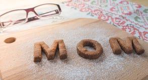 Biscuit de maman de Word au-dessus du fond en bois Le concept d'un parent célibataire Image stock