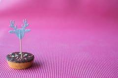 Biscuit de Noël avec le haut de forme décoratif de renne sur le fond rose Images stock