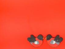 Biscuit de pain d'épice sous forme de bouvreuils doux de biscuits de bouvreuils d'oiseaux sur un fond rouge Photo libre de droits