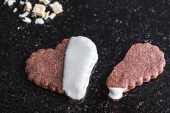 Biscuit en forme de coeur entier de chocolat avec un biscuit brun en forme de coeur cassé sur un compteur de marbre noir, fin  image stock