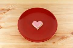 Biscuit en forme de coeur givré d'un plat rouge Photographie stock