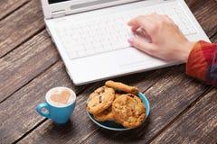 Biscuit et main de femmes Photos libres de droits
