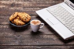 Biscuit et tasse avec l'ordinateur portable Image stock