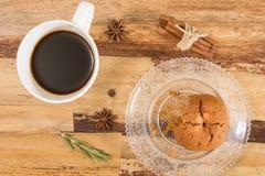 Biscuit et tasse de café mordus, sur la surface en bois Images stock