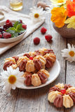 Biscuit with fresh berries on white plate and garden flowers on wooden background. Selective focus. Biscuit with fresh berries on white plate. Selective focus Stock Photo