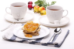 Biscuit with jam and teacup. Biscuit on the plate with apricot jam and tea into the cup Stock Image
