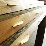 Biscuit joints wood boards. Wooden boards with prepared biscuit joints in woodworker's shop for making a handcrafted table Royalty Free Stock Images