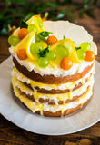 Biscuit layered cake with cream cheese and lemon curd decorated with fresh mint leaves, physalis, lemon slices and green grapes Stock Image