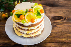 Biscuit layered cake with cream cheese and lemon curd decorated with fresh mint leaves, physalis, lemon slices and green grapes Royalty Free Stock Photos