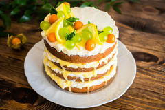 Biscuit layered cake with cream cheese and lemon curd decorated with fresh mint leaves, physalis, lemon slices and green grapes Royalty Free Stock Images