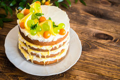 Biscuit layered cake with cream cheese and lemon curd decorated with fresh mint leaves, physalis, lemon slices and green grapes Royalty Free Stock Photo