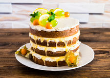 Biscuit layered cake with cream cheese and lemon curd decorated with fresh mint leaves, physalis, lemon slices and green grapes Stock Photography