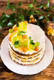Biscuit layered cake with cream cheese and lemon curd decorated with fresh mint leaves, physalis, lemon slices and green grapes Royalty Free Stock Photography