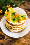 Biscuit layered cake with cream cheese and lemon curd decorated with fresh mint leaves, physalis, lemon slices and green grapes Stock Images