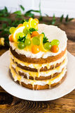 Biscuit layered cake with cream cheese and lemon curd decorated with fresh mint leaves, physalis, lemon slices and green grapes Stock Photos