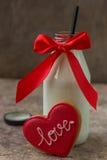 Biscuit pour le jour du ` s de Valentine et bouteille en verre de lait avec la nervure rouge Photographie stock libre de droits