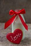 Biscuit pour le jour du ` s de Valentine et bouteille en verre de lait avec la nervure rouge Image stock