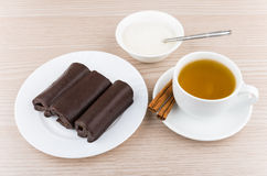 Biscuit roll in chocolate in glass plate, tea, cinnamon sticks Royalty Free Stock Photo