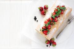 Biscuit roll with mascarpone cream and blueberries decorated strawberries, blueberries and mint leaves Stock Photography