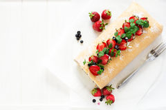 Biscuit roll with mascarpone cream and blueberries decorated strawberries, blueberries and mint leaves Stock Photos
